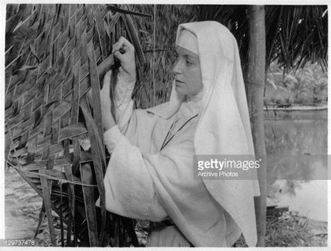 Deborah Kerr adjusting leaves in hut in a scene from the ...