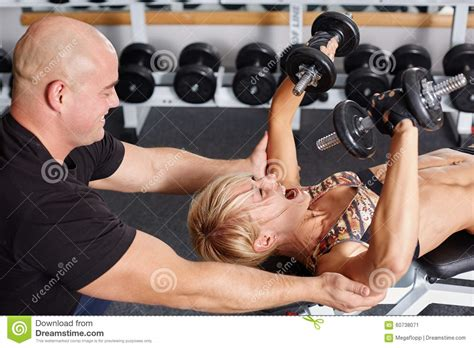 personal trainer helping blonde woman  press