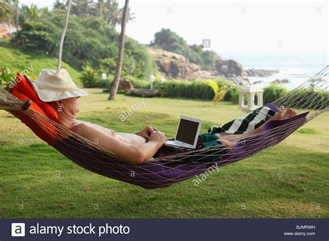 Relaxing In A Hammock by Wearing A Hat Lying In A Hammock And Relaxing While