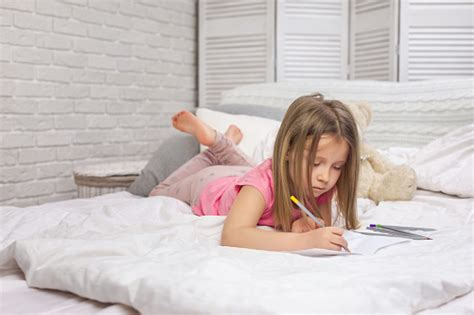 cute  girl drawing pictures  lying  bed stock