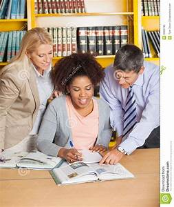 Teachers Assisting Student In College Library Royalty Free ...