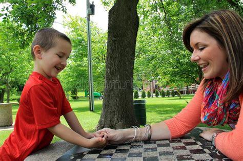 mother  son  fun thumb wrestling stock image