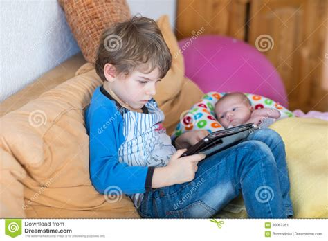 preschool kid boy tablet computer 346 | preschool kid boy playing games tablet computer cute newborn baby looking brother babysitting adorable kids children 86067261