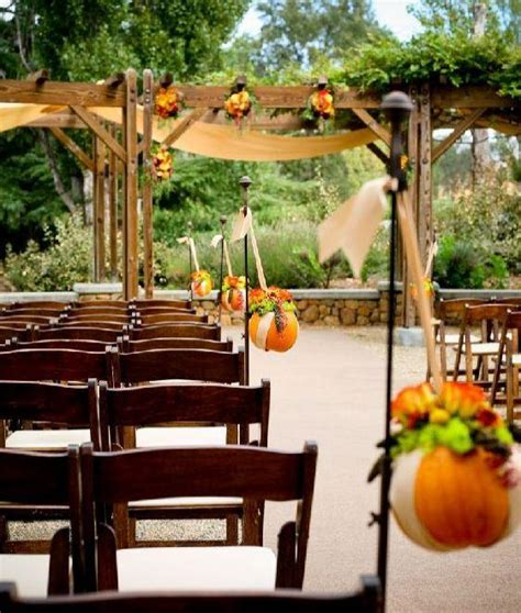 beautiful outdoor wedding ceremony during fall with pumpkin and floral wedding details decor