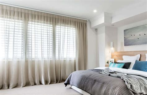bedroom  white walls  neutral sheer curtains