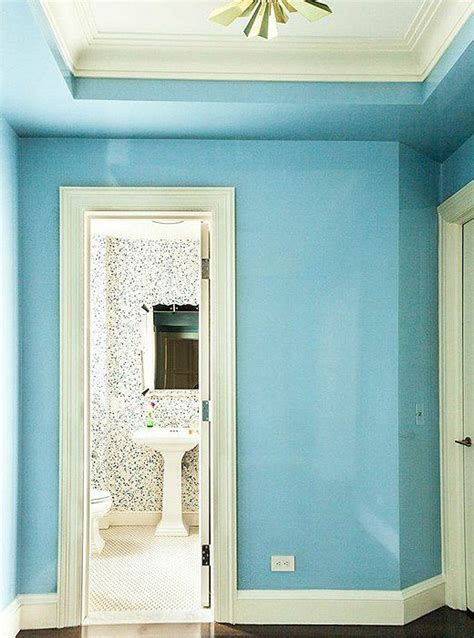 sky blue entry hall with white trim and a brass flush