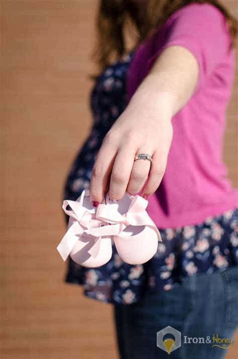 holding baby shoes showing wedding ring with baby bump in the background