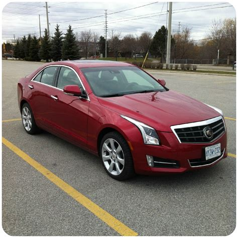 red cadillac driving down the street the cadillac ats