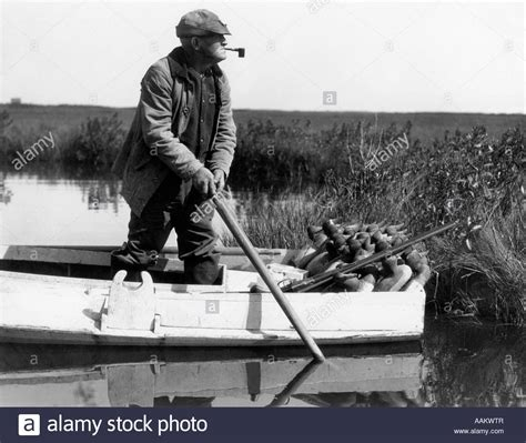 Vintage Duck Hunting Boat by 1920s 1930s Senior Man Duck Hunter Standing In Sneak Box