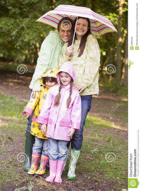 family outdoors  rain  umbrella smiling stock photo