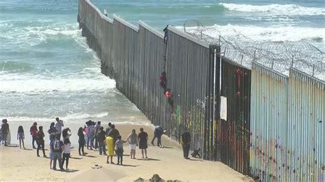 migrants  mexico climb  border fence sbs news