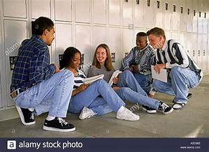 High schools students sitting in hallway of school talking ...