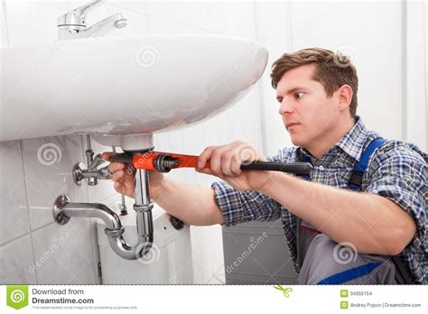 fix a kitchen faucet portrait of plumber fixing a sink stock photo image
