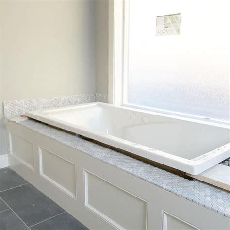 white jetted tub  carrara hexagon honeycomb backsplash