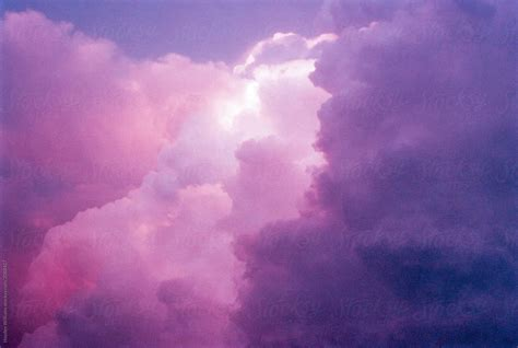 Surreal purple sunset sky filled with clouds by Hayden