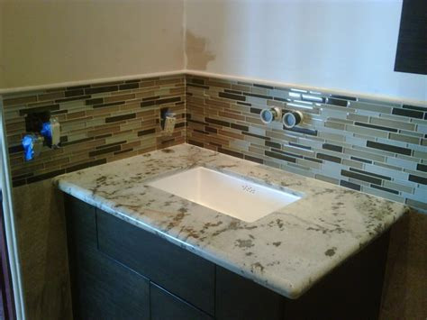 granite counter top with undermount sink and glass tile
