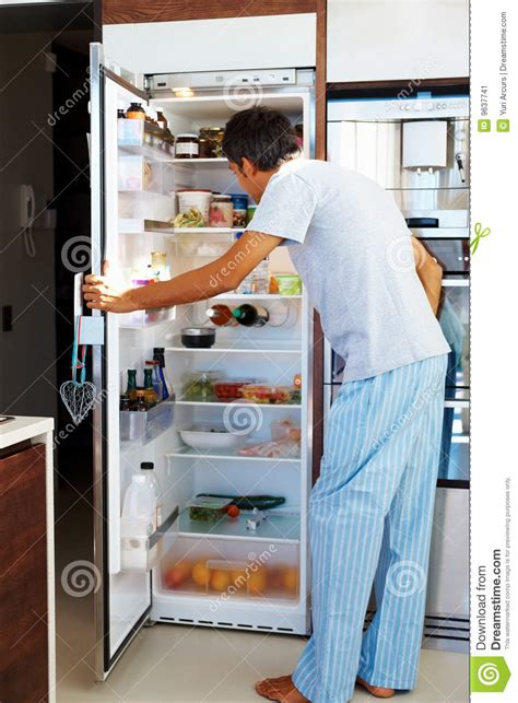 hunger mature man opening  refrigerator door stock