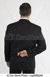 Stock Image of Businessman with fingers crossed behind ...