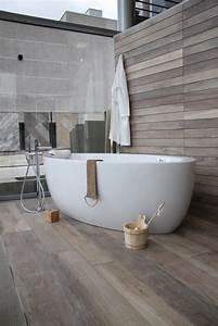 une baignoire ilot en acrylique posee sur un carrelage With parquet de récupération