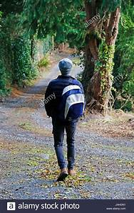 Young man carrying backpack walking away from camera Stock ...
