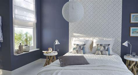 une chambre aux murs gris qui capte la lumiere grace  sa