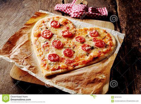 Baked Heart shaped Pizza Topped With Tomato Slices Stock