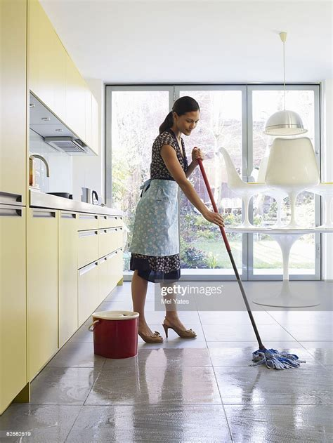 young woman mopping kitchen floor stock photo getty images