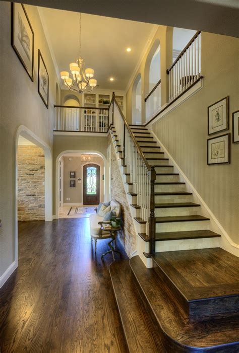 open space stairs leading to front door bathroom at far end of stairs opening under stairs to kitchen framed by