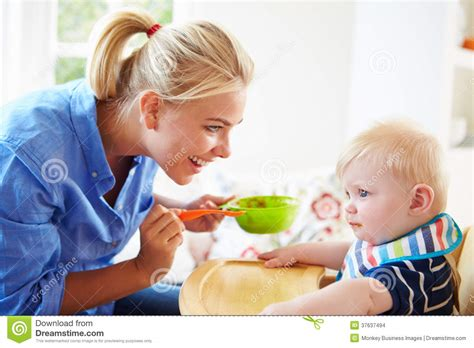 feeding baby boy in high chair stock images image