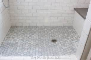 the shower floor is hexagon shaped marble tiles with darker gray grout we had the marble sealed