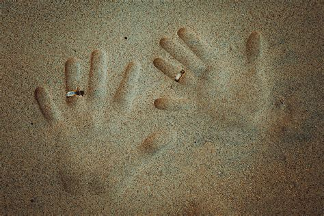 hands  wedding rings   sand photograph