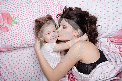 Mum Kisses The Daughter Lying In Bed Stock Photo  Image