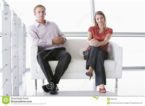 Two Businesspeople Sitting In Office Lobby Smiling Stock