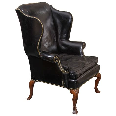 pair of carved and upholstered mahogany wing black leather wing chair at 1stdibs