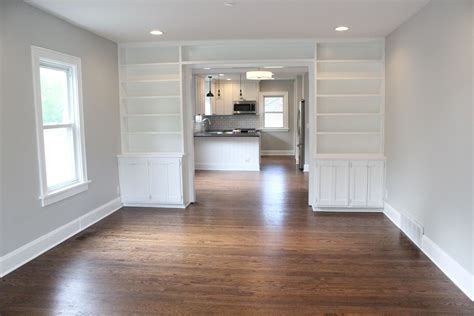 warm brown hardwood floors gray owl paint white built ins renovated living room vintage