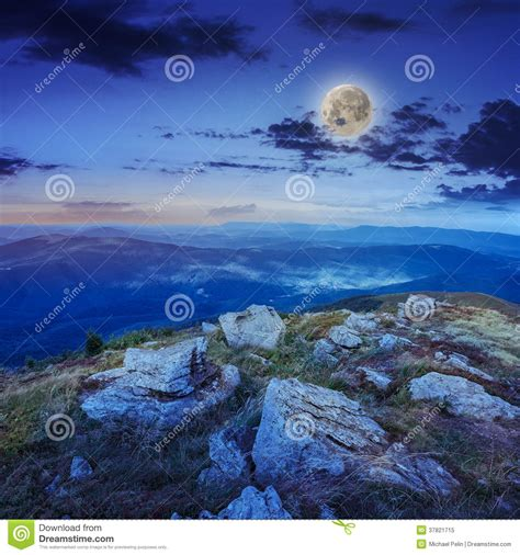 light on stone mountain slope with forest at night stock