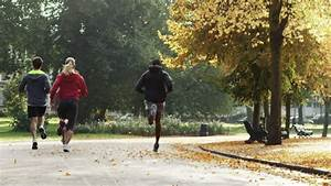 Group Of Runners Running In Park Wearing Wearable