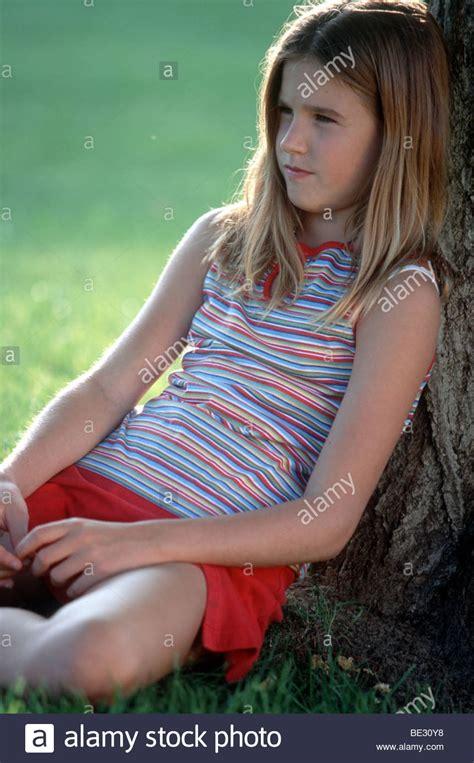 Preteen Girl Sit Against Tree In Park Pensive Mood Stock