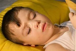 sick boy 3 years old is sleeping on a yellow pillow With best pillow for 1 year old