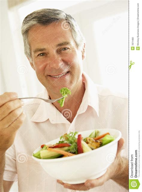 middle aged man eating  healthy salad stock photography