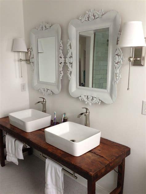 white bathroom  vessel sinks  wood table  vanity