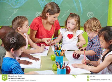 children learning writing stock image image of arts 719 | children learning writing together preschool nursery teacher 38917605