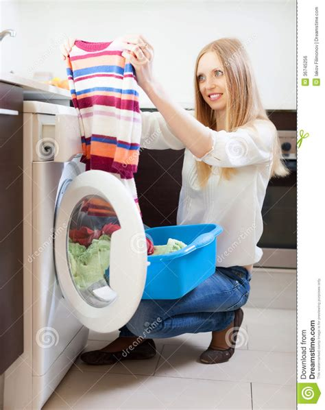 Woman Looling Clothes Near Washing Machine Stock Photo