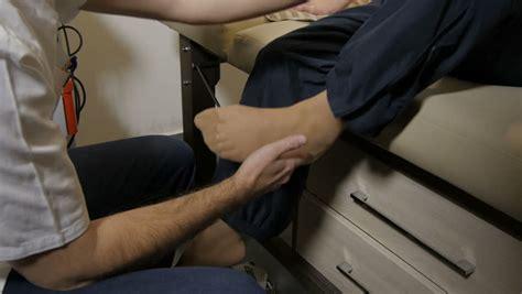 Therapist Exercising Older Woman Injured Leg