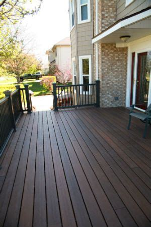 restaining deck same color shows light vinyl siding against brown brick with the