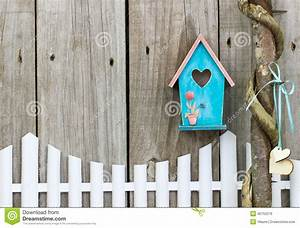 Teal Blue Birdhouse Hanging Over White Picket Fence Stock