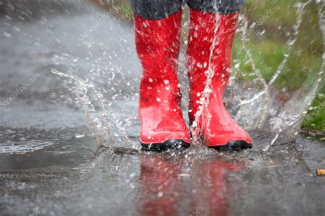 red rubber boots  jumping   big puddle stock