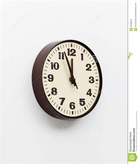 horloge de brown sur le mur blanc de bureau près du midi