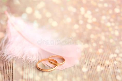 Wedding Background With Gold Rings, Pink Feather And