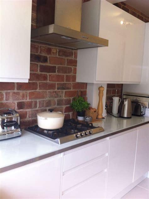exposed brick kitchen  clean gloss white units